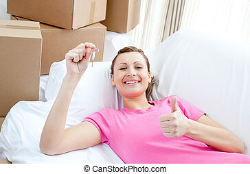 Positive woman relaxing on a sofa with boxes at home