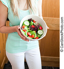 Beautiful woman showing a salad
