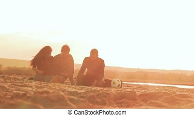 friends sitting on the sand with laptops and laugh slow...