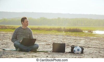 man with a laptop on the sand slow motion video - at sunset...