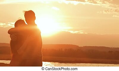 a man embraces the girl on a sunset background Slow motion video