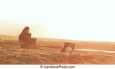 sits on the sand and woman working behind the laptop slow motion video