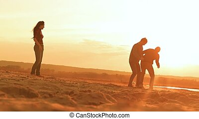 in the evening men play ball on the beach slow motion video...