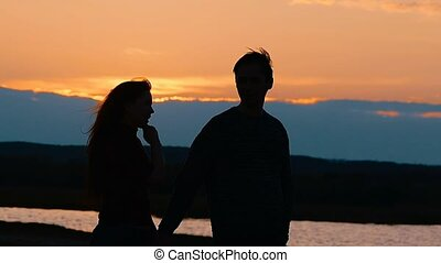 silhouette of girl and man holding hands slow motion video -...