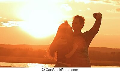 at sunset man and woman hugging slow motion video