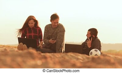 sitting on the sand with three friends laptops slow motion...