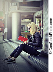 girl reading red book - young hipster girl reading a red...