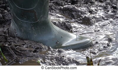 a man in rubber boots walking on the mud HD video