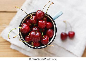 Fresh juicy sweet cherries in old rusty mug. Rustic...