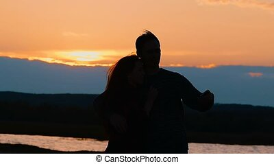 silhouettes of a couple at the lake makes selfie slow motion...