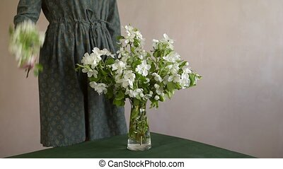 Woman putting a twig into vase