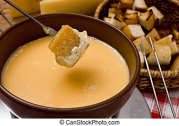 Cooking cheese fondue - Cheese fondue – piece of bread...