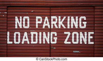 No parking loading zone sign on red metal door