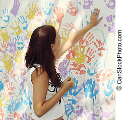 Girl stamps trace hands on wall with prints - Girl stamps...