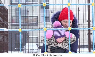active woman with baby girl enjoy snow fall blizzard in...