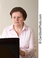 Senior at computer - A beautiful senior woman using the...