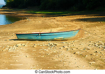 Small old fishing boat on a lake shore.