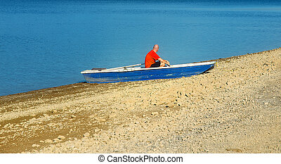 Small old fishing boat on a lake shore and man.