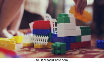 Kids playing constructor. Children playing with colorful plastic blocks.