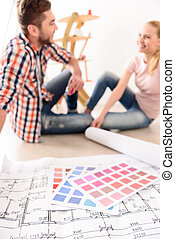 Cheerful couple discussing construction house plan