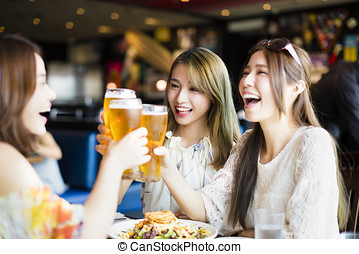 Group of girl friends toasting and eating in the restaura -...
