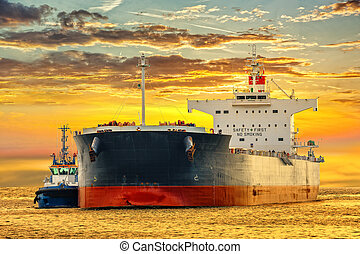 Tugboat and tanker ship - Tanker ship on sea in the rays of...