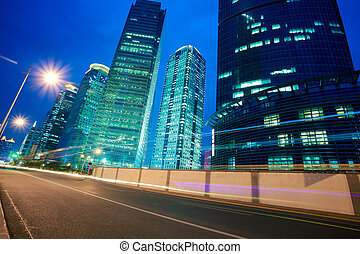 Road light trails on streetscape office buildings in...