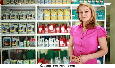 seller in the store helps girl to choose engine oil. - Young...