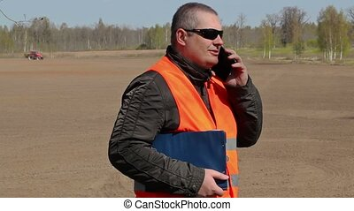 Farmer talking on smart phone at the field where the tractor...