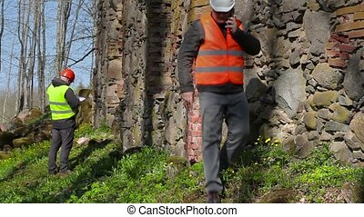Building inspector talking on smart phone near ancient wall...