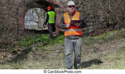 Building inspectors at old ruins before restoration