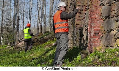 Building inspector filming near ancient wall