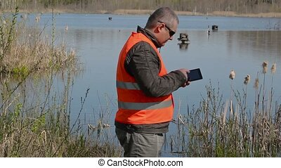 Ornithologist using tablet PC near the duck's houses at the...