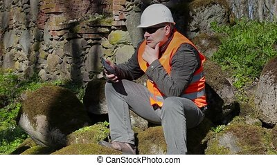 Building inspector thinking near ancient wall