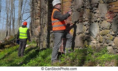 Building inspector take pictures near ancient wall before...