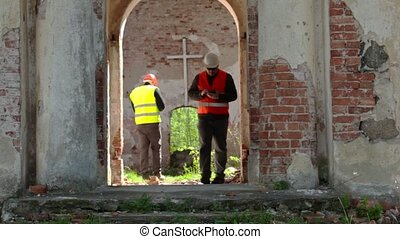 Building inspector take pictures on tablet PC at old church...