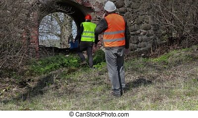Building inspector talking on smart phone at old ruins...
