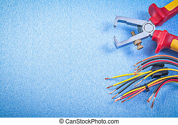 Insulated wire strippers electrical cables on blue...