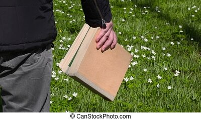 Man with books on green meadow
