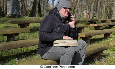 Man with two books and smart phone on bench in park
