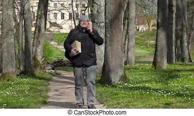 Man with two books talking on smart phone and walking in the...