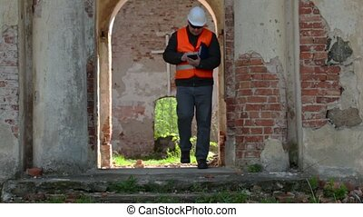 Building inspector using tablet PC at old church before...