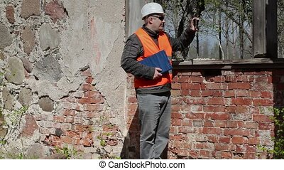 Building inspector take pictures on tablet PC near window