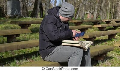 Man using tablet PC and reading books on bench in park