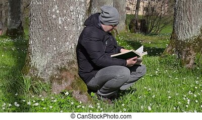 Man reading book in meadow near tree