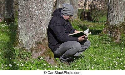 Man reading book in meadow near