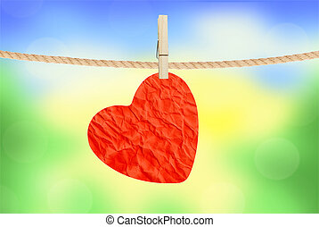 Crumpled paper heart hanging on rope on nature background