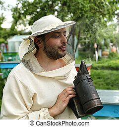 beekeeper in protective clothing holding smoker while...