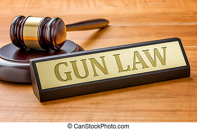 A gavel and a name plate with the engraving Gun Law