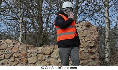 Building inspector talking on cell phone at the ruins of old...